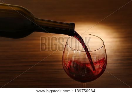 Red wine pouring in glass on wooden background