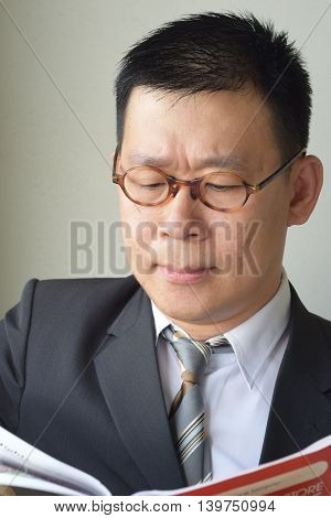 An asian business man frowning while looking at a report
