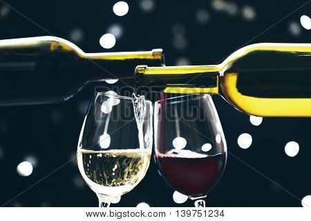 Red and white wine pouring in glass on bokeh background