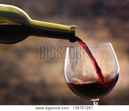 Red wine pouring in glass on brown background