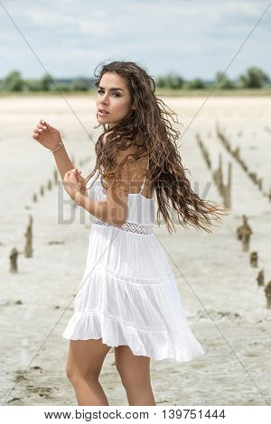 Young girl stands sideways on the sand on the nature background. She wears white dress. She holds her hands in front of herself. She looks into the camera with parted lips. There are wooden pillars on the sand behind the girl. Outdoors. Vertical.