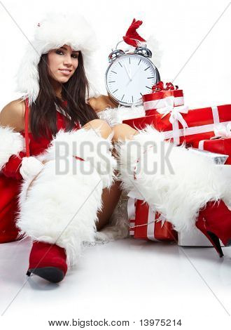 Photo of Santa girl pointing at clock showing five minutes to midnight