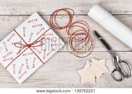 Christmas present stamped with the word Merry. High angle shot with scissors, twine and roll of wrapping paper.