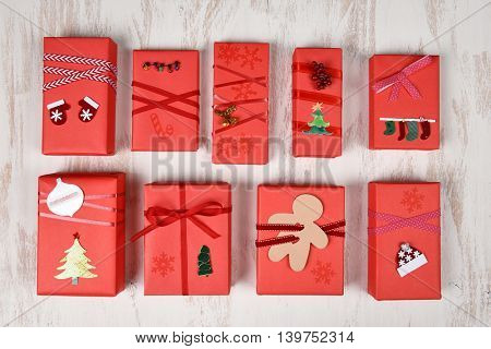 Top view of a group of Christmas presents wrapped in red paper and decorated in various designs.