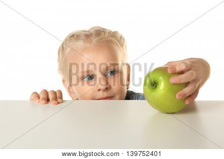 Funny little girl hiding behind white table and looking at apple