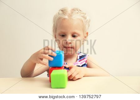 Funny little girl hiding behind white table and taking colourful cubes