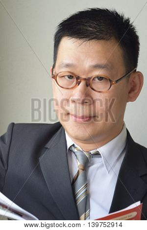 An asian business man browsing a report while looking at the camera