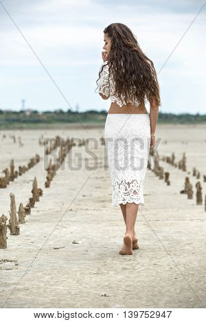 Pretty barefoot girl stands sideways on the sand on the cloudy sky background. She wears a white lacy top and a white lacy skirt. She holds her hands along the body. She looks into the camera. There are wooden pillars on the sand behind the girl. Outdoors