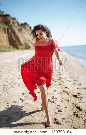 Attractive girl in a smart dress red goes along the seashore. Curly hair fluttering in the wind.