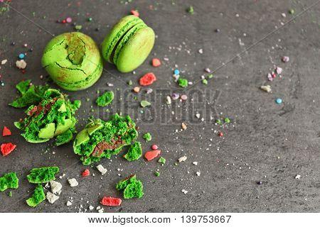 Green broken tasty macaroons on gray background