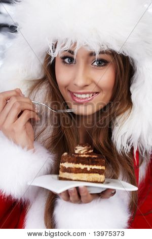 Christmas girl in red santa hat eating cake on plate