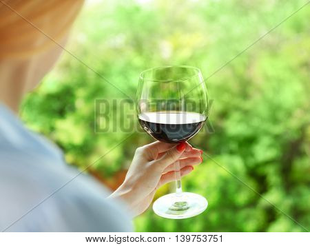 Woman holding glass of wine on blurred natural background
