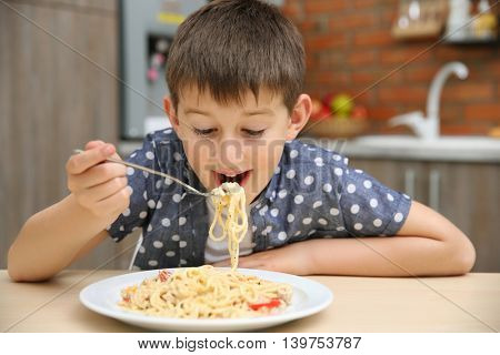 Cute boy eating spaghetti on kitchen