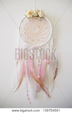 photo of a handmade white pink native american dreamcatcher with feathers, paper flowers, beads and lace