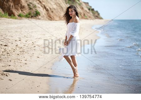 Attractive brunette in white polka-dot dress walks on the sandy sea beach. In the hands of beauty holds wide-brimmed hat. Sunny day, curly haired girl flowing on a wind.