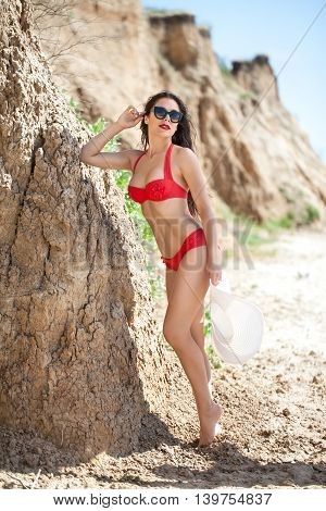 Sexy brunette in a bright red bathing suit and sunglasses on the sandy sea beach. The girl attractive sports figure. On his head wearing a white hat with long fields.