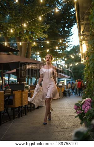 Sexy brunette with curly hair walking in the evening city. A girl wearing a pink dress is easy. Against the backdrop of lights and life of the city of Odessa, Ukraine.