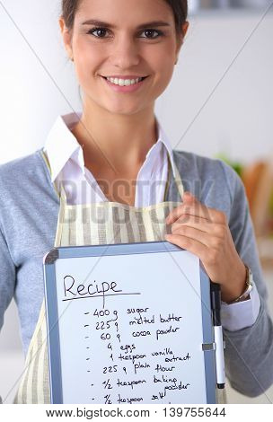 Woman in the kitchen at home, standing near desk