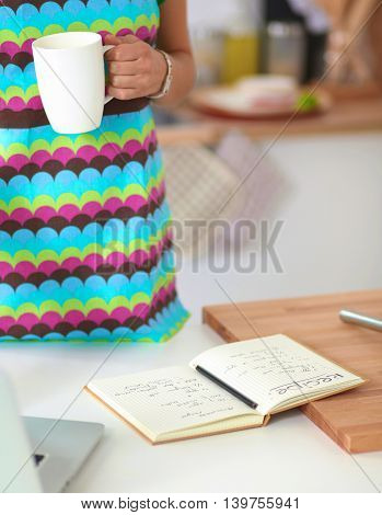 Smiling woman in the kitchen, isolated on  background