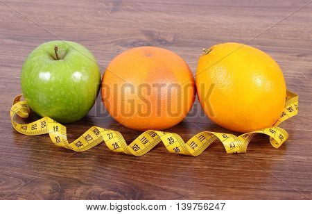 Fresh ripe fruits and tape measure on wooden board grapefruit orange apple healthy lifestyles nutrition and strengthening immunity
