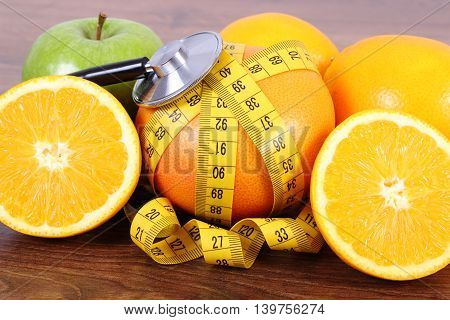 Medical stethoscope and tape measure with fresh ripe fruits on wooden board grapefruit orange apple healthy lifestyles and nutrition