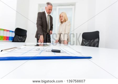 Business people at work. Focus on the pen.