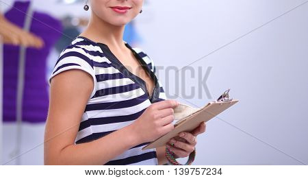 Smiling fashion designer standing near mannequin in office isolated