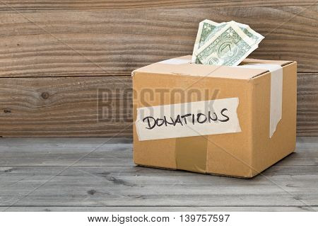 Donation carton box with dollar bills on wooden table background