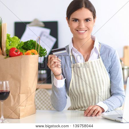 Woman online shopping using computer and credit card in kitchen