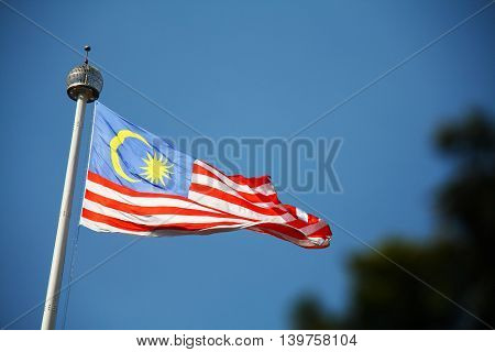 Malaysia national flag at the top of the pole with clear blue sky