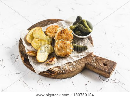 Fish balls and baked potatoes on wooden cutting board on white background
