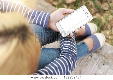 woman sitting and holding phone white screen in park