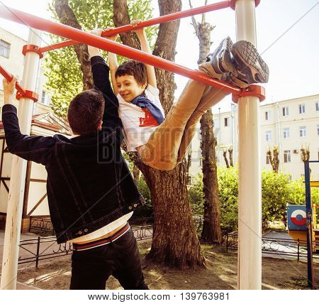 Father with son on playground training, happy real family smiling outside, lifestyle people concept close up