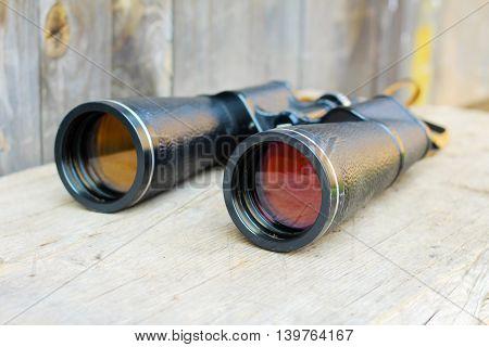 black binoculars. Big telescope on wooden background.