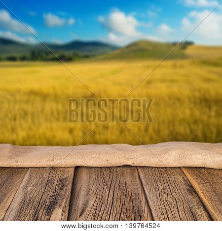 Blurred field of wheat as agricultural background. In the foreground a wooden table