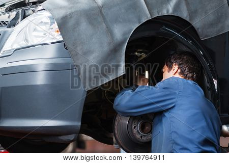 Repair man fixing car suspension system at garage. Mechanic working near automobile without wheel, service maintenance at workshop