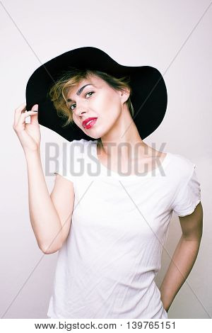 Studio photo of a beautiful girl in a black hat and red lips.