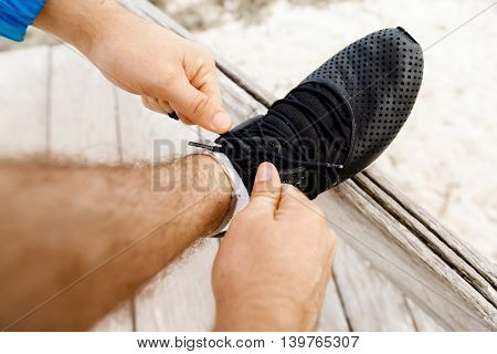 Runner laces his shoes and prepares to jogging
