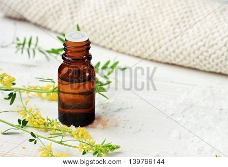Bottle of essential oil, green herbs, sea salt scattered, beige cotton towel. Herbal extract for skincare.