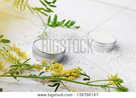 Facial herbal cosmetic cream in containers, fresh aromatic meadow herbs, sea salt scattered on white board. Chemical-free moisturizers.
