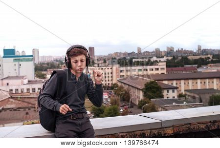 teenager on the roof of the house listens to music