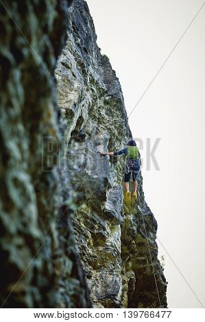 male rock climber. climber climbs on a rocky wall. man hanging on a rope