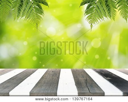 Wood table for display product and blurry green in background. Fern hanging down on table.