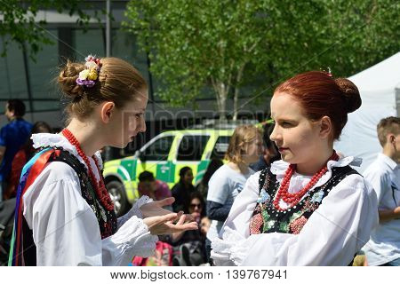 LONDON ENGLAND 9 May 2015: Two girls in traditional polish costume chatting