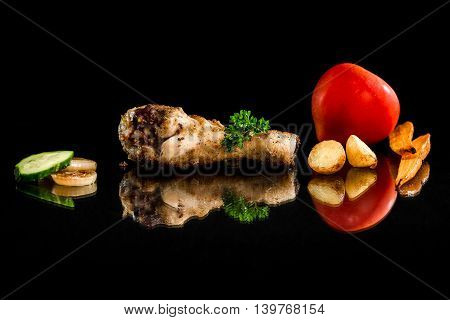Roasted chicken drumstick and vegetables on the black background