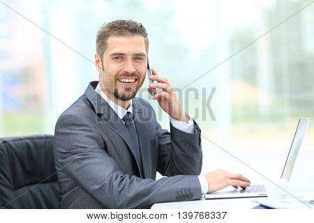 Salesman working on laptop and talking on phone