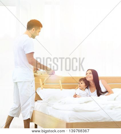 Smiling family having breakfast sitting on bed at home