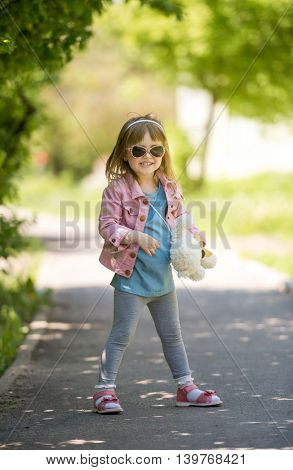 smiling little girl with sunglasses walking in spring park