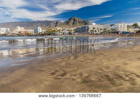 TENERIFE SPAIN - January 23 2016: Crowd of people swimming and sunbathing on the picturesque Playa de Troya beach of Costa Adeje resort.