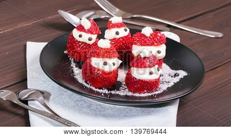 New Year's snack from strawberry and cream. Santa-Claus on a strawberry berries dish. Close up small depth of sharpness